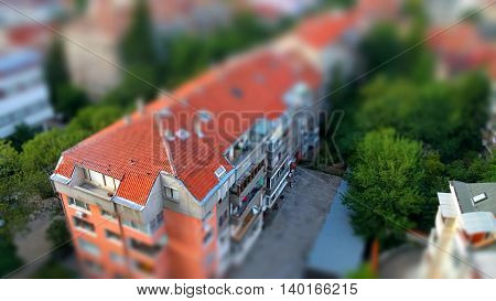 Cute toy like miniature tilt-shift effect photo of red ceramic tiling roof of a residential building