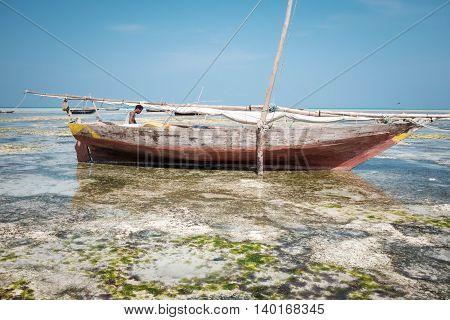 NUNGWI, ZANZIBAR/TANZANIA - JANUARY 26: Man in the fishing boat near Indian ocean coast on January 26, 2016 in Nungwi, Zanzibar/Tanzania