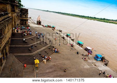 Maheshwar, India - 16th July 2016: People climbing down the huge flight of stairs at the bank of the Narmada river from the Maheshwar fort in Madhya Pradesh
