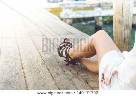 Beatiful woman legs on a natural wooden background with high heeles shoes. Fashion background. Cropped image of pretty young woman