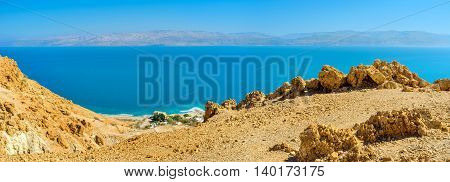 The yellow rocks of Judean Desert with the bright blue waters of the Dead Sea on the background Ein Gedi Israel.