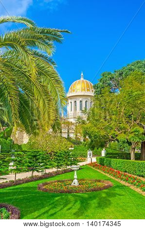 The Bahai Shrine surrounded by paradisiacal garden with shady palms trimmed bushes and colorful flower beds also decorated with small sculptures and fountains Haifa Israel.
