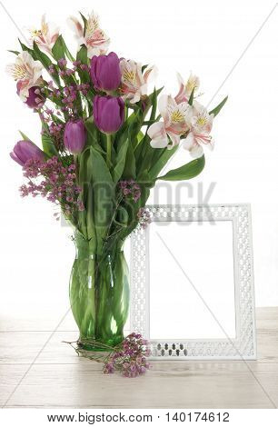 Vase of fresh spring tulip flowers with an empty white painted  metal photo frame.