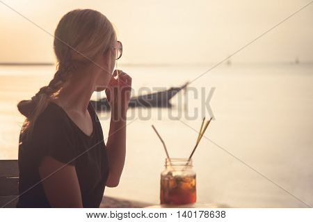 Pensive woman tourist on the beach during holidays looking into the distance towards horizont and sunset sky. Woman siiting in beach café with cocktail and copy space