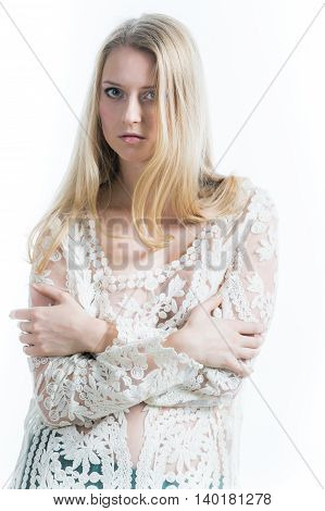 blonde girl on a white background in a white translucent blouse