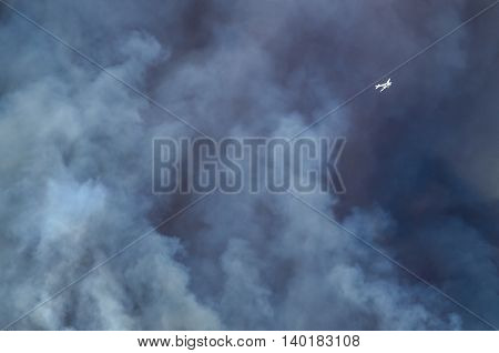 White Aircraft Flying Ahead of the Dense White Smoke Rising from the Raging Wildfire