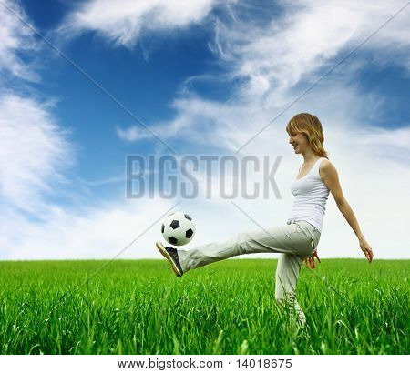 Young woman playing with ball on green meadow