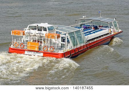 LONDON UNITED KINGDOM - JULY 1 2014: A City Cruises tour boat sails on the Thames River. Thames is the longest river in England with 346 km (215 miles) long.