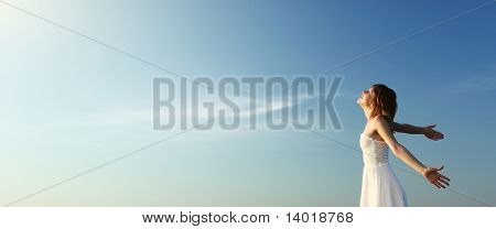 Young woman in white dress over blue sky background enjoying the sun