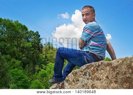 Young man dangerously sitting at the edge of the cliff and enjoying the picturesque view