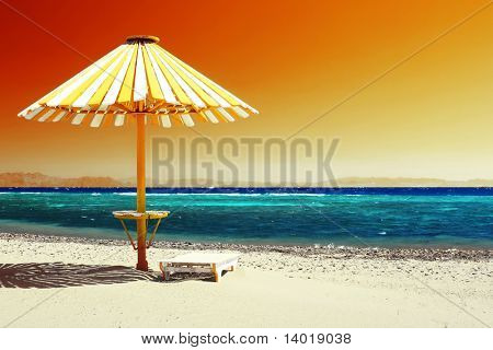 Wood umbrella on beach with clear red sky