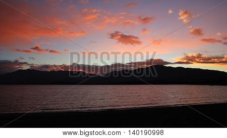 Sunset in the Southern Alps New Zealand. Dramatic sky over Lake Tekapo and mountains.