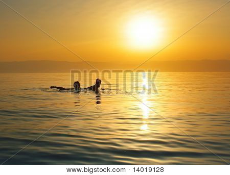 Woman swimming in salty water of a Dead Sea