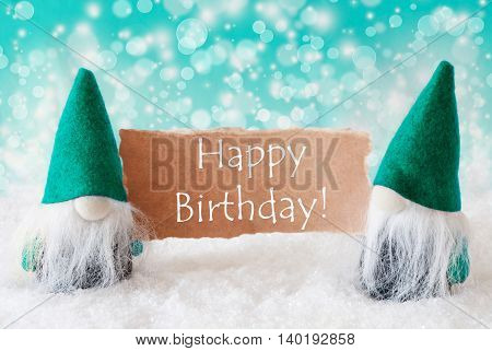 Christmas Greeting Card With Two Turqoise Gnomes. Sparkling Bokeh Background With Snow. English Text Happy Birthday