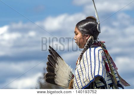 Coeur d'Alene Idaho USA - 07-23-2016. Side view of Native American against blue sky. Young dancer participates in the Julyamsh Powwow on July 23 2016 at the Kootenai County Fairgrounds in Coeur d'Alene Idaho.