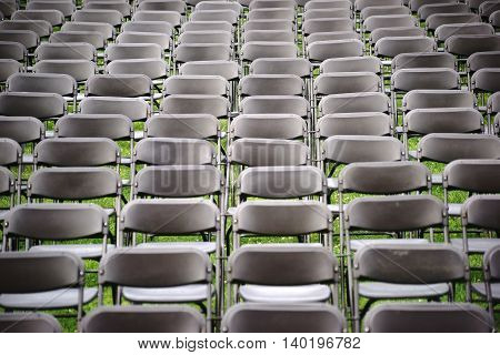 Parallel arranged empty seat rows of folding chairs on a lawn before a concert.