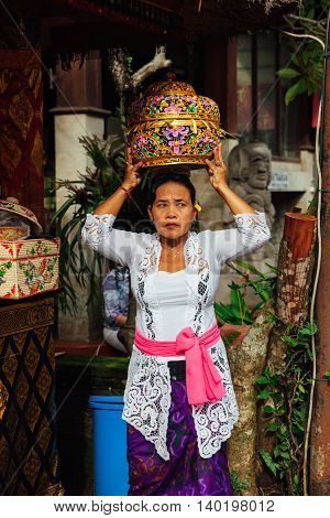 UBUD INDONESIA - MARCH 2: Woman with basket on the head during the celebration before Nyepi (Balinese Day of Silence) on March 2 2016 in Ubud Indonesia.