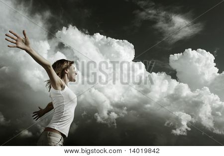 Young woman with raised hands over stormy clouds background