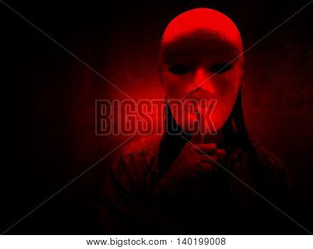Mysterious woman wearing white mask and gesturing finger silence,Scary background for book cover