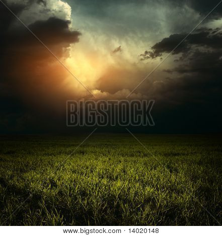 Storm clouds over green meadow with grass