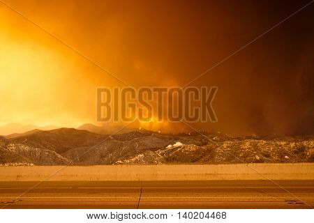 Wildfire in the mountains near freeway. Brush fire. Forest fire.