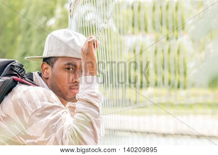 asylum seeker refugee holding the barricade looking hopeful to obtain visa - concept of refugee crisis