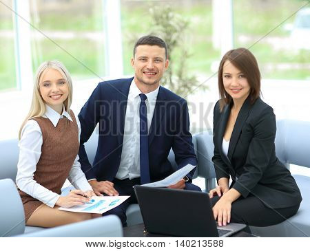 Successful businessteam of three sitting in office and planning