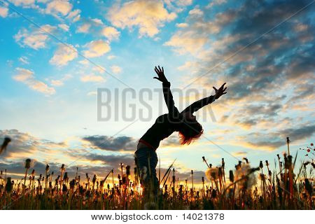 Young woman with raised hands standing on meadow with herbs on sunset