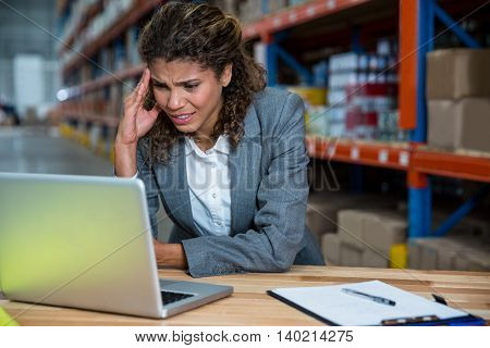 Business woman is stressed because of work in a warehouse