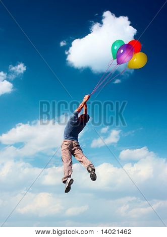 Young man flying in blue sky holding group of bright balloons