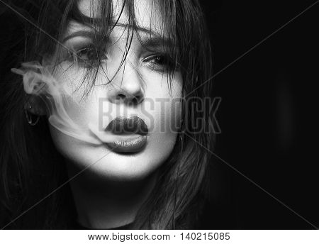 Beautiful sexy brunette girl with bright makeup, red lips, smoking with smoke from mouth. beauty face. Black and white. Photos shot in the studio on a black background.