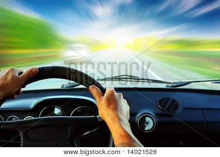 Hands on steering wheel of a car driving on an asphalt blurred road