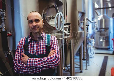 Portrait of mature manufacturer with arms crossed standing by storage tanks at brewery
