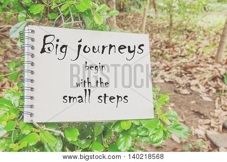 Word  Big Journeys Begin With The Small Steps.inspirational Motivational Quote On Paper In The Tree