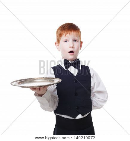 Little waiter stands with tray serving big double hamburger. Smiling redhead child boy in suit plays restaurant servant, gives burger at blue background