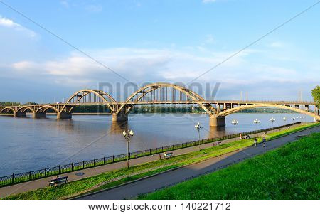 RYBINSK RUSSIA - JULY 21 2016: Unidentified people walk along Volga embankment near automobile bridge over Volga River Rybinsk Russia