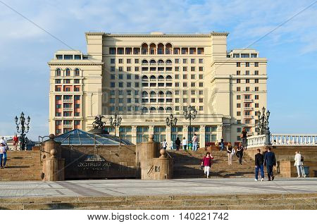 MOSCOW RUSSIA - JULY 23 2016: Unidentified people walk on Manezhnaya Square near famous prestigious building of Four Seasons Hotel Moscow 5 * (previously - hotel