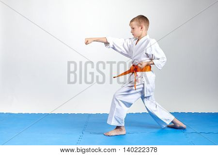 Sportsman in rack karate beats gyaku-tsuki on the mats