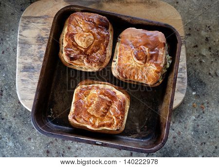 Savoury meat or vegetable pies with flaky puff pastry on a baking sheet. Photographed in New Zealand NZ.