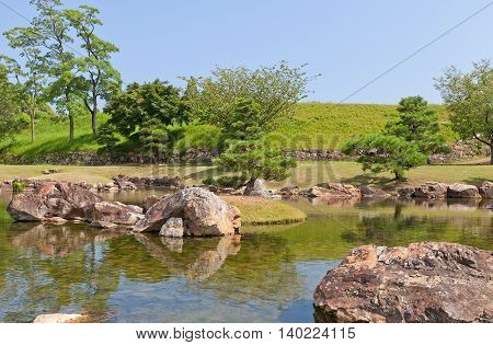 AKO JAPAN - JULY 18 2016: Pond and garden (restored in 1986) of main bailey (Honmaru) of Ako Castle (circa 17th c.) in Ako Japan. Castle was a seat of Lord Asano Naganao