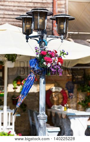 Old town street view with colorful decorated streetlight, umbrella and flowers