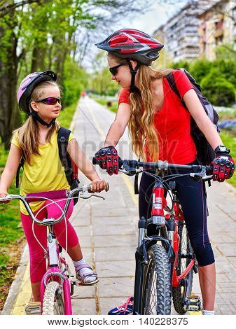 Bikes bicyclist girl. Girls wearing bicycle helmet and glass with rucksack cycling bicycle. Girls children cycling on yellow bike lane. Bicycle girl talk each other.