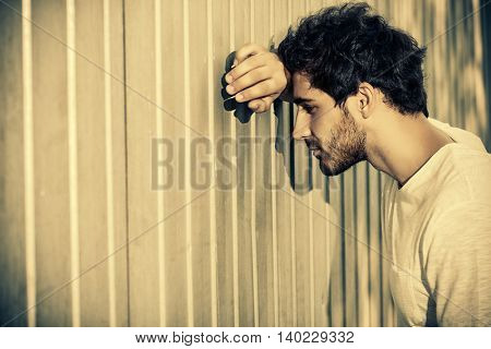 Young brunet man leaning to the wall. Urban background.