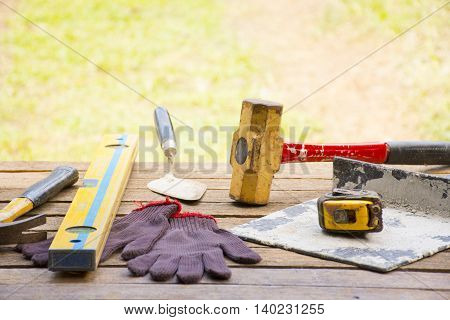 Masonry tool background such as glove and tape measure and sledgehammer with trowel and level and etc.Background for craftsman tool or background for building.4
