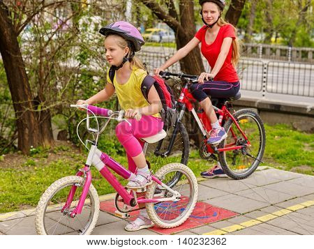 Bikes bicyclist girl. Two sisters girls wearing bicycle helmet with rucksack ciclyng bicycle. Girls cycling on yellow bike lane. Bike share program save money and time at city street. Summer outdoor. poster