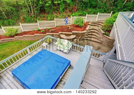Two Level Backyard Deck With Jacuzzi On The First Floor And Patio Area On The Second One