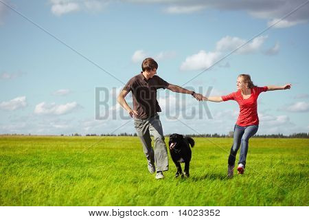 Young happy pair running on green meadow with a dog