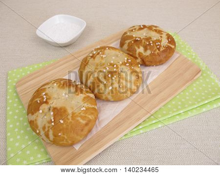 Homemade lye rolls covered with salt on wooden board