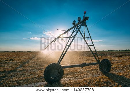 Automated agricultural center pivot irrigation system with drop sprinklers in harvested wheat stubble field in late summer afternoon retro toned poster