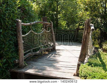 Wood bridge with rope for walking through the garden